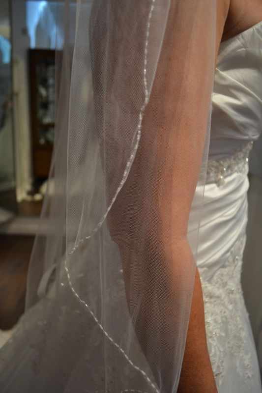 I am wearing a two tier scalloped edge fingertip length veil with beading